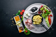 English breakfast. Eggs, olives, fresh vegetables, nuts, dried fruit and honey. Top view. Free space for text. On a wooden background.