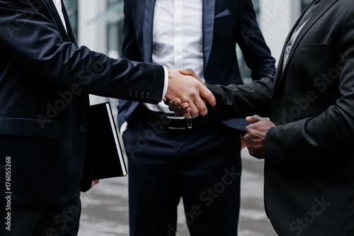 Fototapeta  Handshake of business partners. Three businessmen close-up