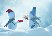 Merry Christmas And Happy New Year Greeting Card .Two Cheerful Snowmen  Standing In Winter Christmas Landscape.