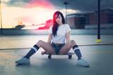 Trendy young woman sitting on skateboard in sunset