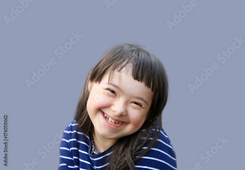 Photo  Cute smiling down syndrome girl on the blue background
