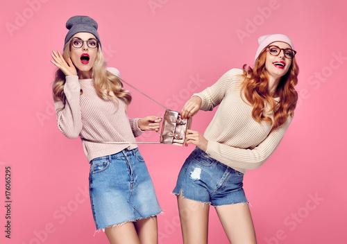 Plakat Młoda kobieta zaskoczony uśmiecha się. Zabawa szalona. Moda. Pretty Sisters Best Friends Twins w stylowym stroju jesienno-zimowym. Zabawne dziewczyny z Hipster. Cool Blond Redhead w wygodnym swetrze na różowo