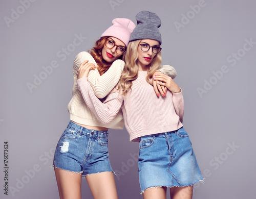 Plakat Moda. Młoda piękna kobieta w stylowy strój jesień przytulanie. Pretty Sisters Best Friends Twins. Hipster Blond Redhead Model, fashion Cozy sweter, okulary. Dziewczyny w modnej czapce. Kolor wanny