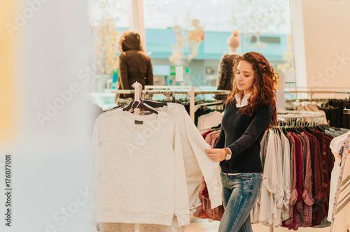 Plakat Młoda dziewczyna w sklepie kupując ubrania.