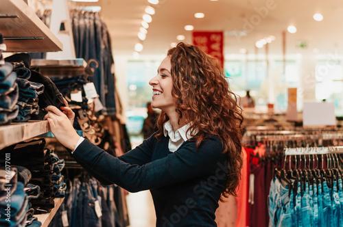 Plakat Radosny młodej kobiety wybierać odziewa w sklepie.