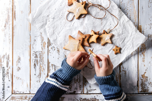 Tuinposter Koekjes Child hands make garland of homemade shortbread star shape sugar cookies different size on thread on baking paper over white wooden plank table. Christmas handmade gift. Top view with space