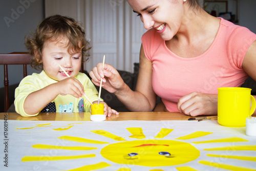 The babysitter is drawing with the baby Canvas Print