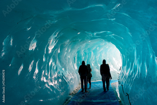 Glaciers Silhouettes of people visiting thee ice cave of the Mer de Glace glacier, in Chamonix Mont Blanc Massif, The Alps, France