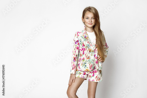 82fcfb0de Beautiful stunning little blonde girl in elegant summer flowers clothing  standing on a white background