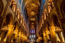 Mystical Image Of The Interior Of Notre Dame Cathedral In Paris With Candles Of Lit Faithful Illuminated By Colored Stained Glass Windows