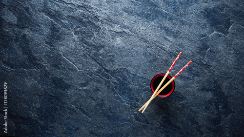 Poster Sushi bar Chopsticks and bowl with soy sauce on textured background