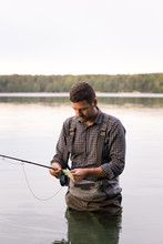 A Man In Waders Is Fly Fishing In A Lake.