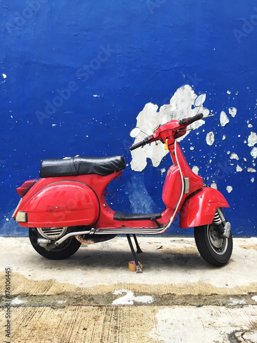 Foto op Canvas Scooter Vintage red scooter against blue wall