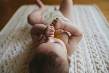 Cute Young Baby Lying On Blanket On Floor - Holding Soother