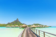canvas print picture Overwater pass to villas on a tropical lagoon of Bora Bora Island, Tahiti, French Polynesia