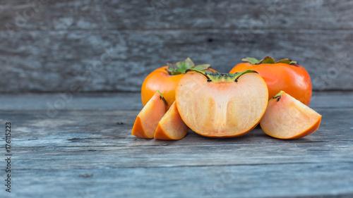 ripe persimmon on wooden background © NIRUN