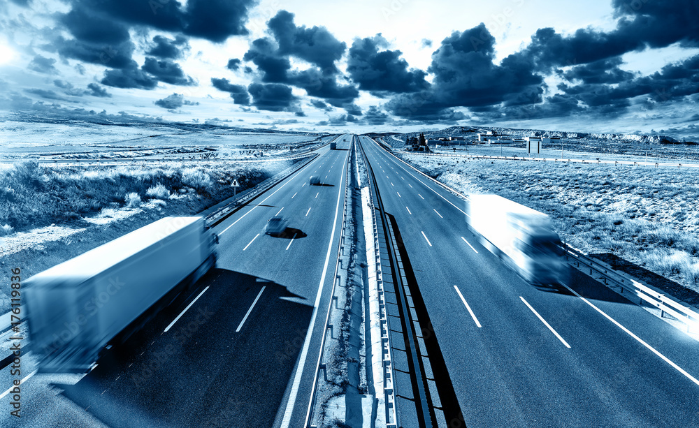 Fototapeta Camiones y autovia.Transporte internacional y logistica.Mercancia llegando a su destino por carretera.