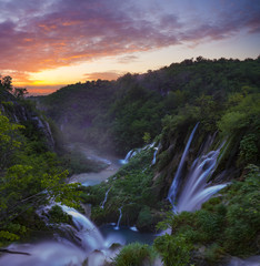 Fototapeta Rzeki i Jeziora foggy and multicolored dawn over beautiful waterfalls in the park of plitvice lakes in croatia