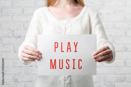 Spoed Foto op Canvas Muziekwinkel Woman holding banner of play passion leisure activity