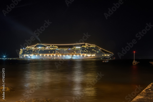 Photo  A huge cruise ship at night stands at anchor glowing with very bright lights