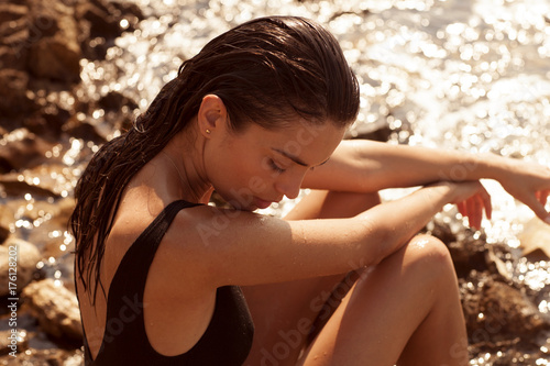 Beautiful girl is posing on the rocks and stones at the seaside. Wallpaper Mural