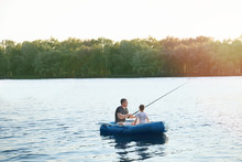 Father With Son Fishing From B...