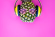 Leinwanddruck Bild - Pineapple in sunglasses and headphones on pink background top view copyspace
