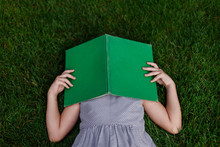 School Girl Laying In Grass With A Green, Vintage Book Over Her Head