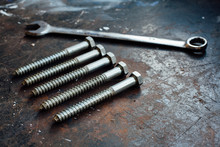 Screw Bolts And Wrench On Worn Work Table