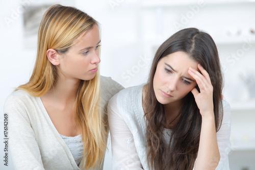 Plakat przygnębiona nastolatka, podczas gdy jej bliska dziewczyna ją uspokaja