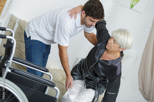 nurse helping disabled lady sitting on her wheelchair Fototapete