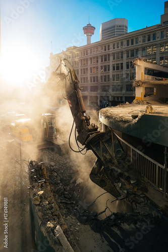 Photo An excavator demolishes a parking structure.