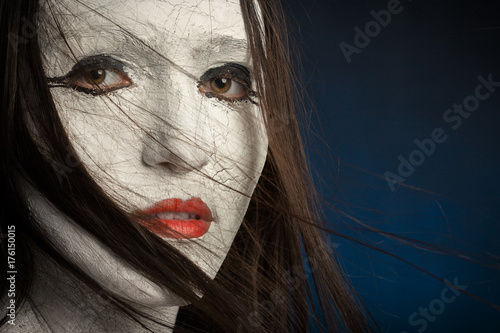 Fototapeta dziewczyna z białymi pęknięty makijaż na niebieskim tle