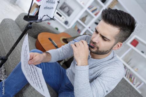 Zdjęcie XXL młody człowiek z książką do komponowania muzyki z gitarą