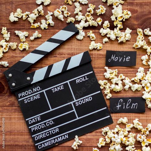 klaps-filmowy-z-rozsypanym-dookola-popcornem-lezacy-na-deskach