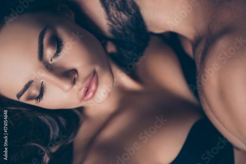 Zamknij przycięte zdjęcie pięknej młodej brunetki kaukaskiej ładnej kobiety w seksownym czarnym staniku z zamkniętymi oczami, tak gorącej i kuszącej, atrakcyjnej i uwodzicielskiej, cieszącej się ze swoim kochankiem