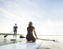 Couple Paddle Boarding At Sunset.
