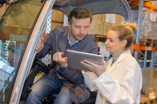 Plakat Pani udzielająca instrukcji od tabletu do kierowcy wózka widłowego