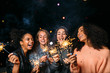 canvas print picture - Outdoor shot of laughing friends with sparklers, standing together at night
