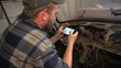 Auto mechanic looks at smartphone how to make electrical wiring in car
