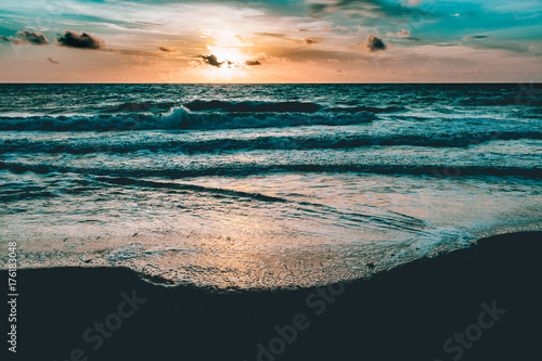 bright sun rising in the colorful sky over dark sand and waves