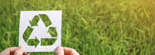 Cut Paper With The Logo Of Recycling Over Green Grass. Recycling Sign And Symbol Background Banner Concept