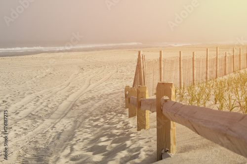 Empty beach at lonely oceanside with warm emotional bright sun pouring into the frame.  Wooden railing and waves in the distance.  Copyspace room for text.