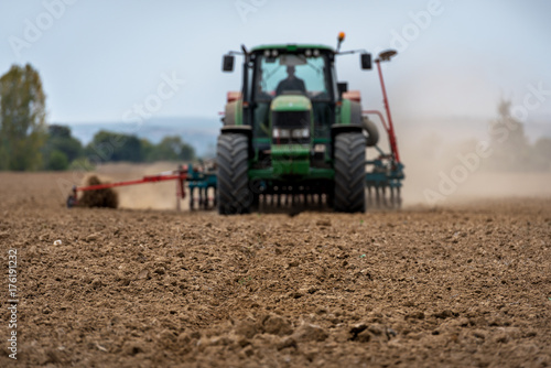 Vászonkép  Close-up of crop with Tractor ploughing field in the background