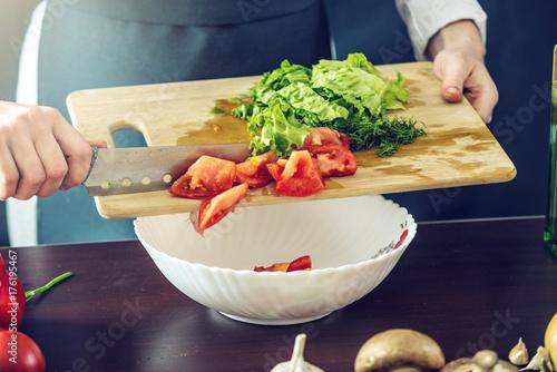 Plakat Szef kuchni w czarnym fartuchu tnie warzywa. Koncepcja ekologicznych produktów do gotowania
