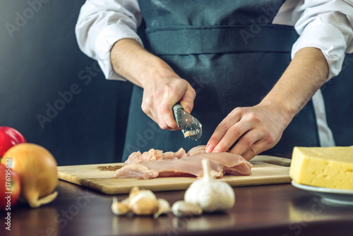 Poster Cuisine The chef in black apron cuts chicken fillet knife. Concept of eco-friendly products for cooking
