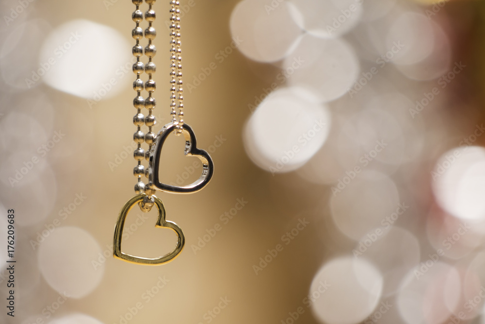 Fototapeta two hearts pendant necklace with glowing blurred background