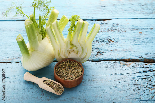Ripe fennel bulbs and dry seeds in bowl and scoop on blue wooden table