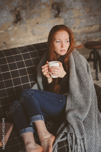 Fotografia  young sick woman healing with hot drink at home on cozy couch, wrapped in knitte