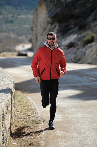 Plakat Sporty mężczyzna bieg na halnej drodze w późnej zimie. Zdrowy trening na świeżym powietrzu.